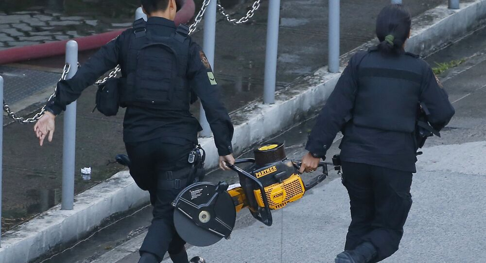 SWAT members of the Philippine National Police rush towards the Resorts World Manila complex with a chain saw in suburban Pasay city, southeast of Manila, Philippines Friday, June 2, 2017