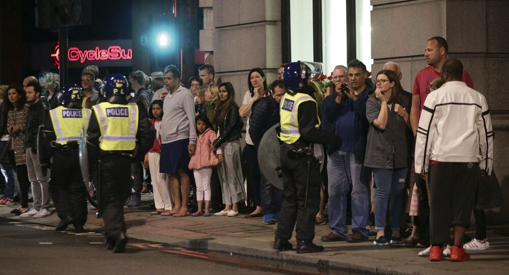 Guests from the Premier Inn Bankside Hotel are evacuated and kept in a group with police on Upper Thames Street following an attack in central London, Saturday, June 3, 2017