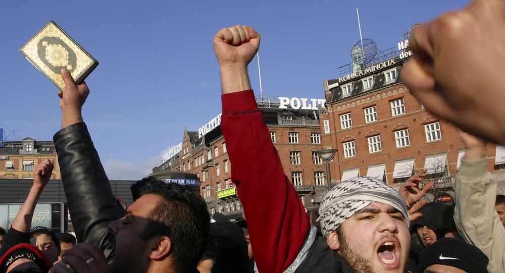 Muslims gesture as one holds a Quran, during a protest against the publication by a Danish newspaper Jyllands-Posten of caricatures of the Prophet Muhammad, outside the City Hall, in Copenhagen, Denmark (File)