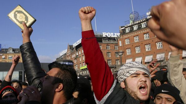 Muslims gesture as one holds a Quran, during a protest against the publication by a Danish newspaper Jyllands-Posten of caricatures of the Prophet Muhammad, outside the City Hall, in Copenhagen, Denmark (File) - Sputnik International