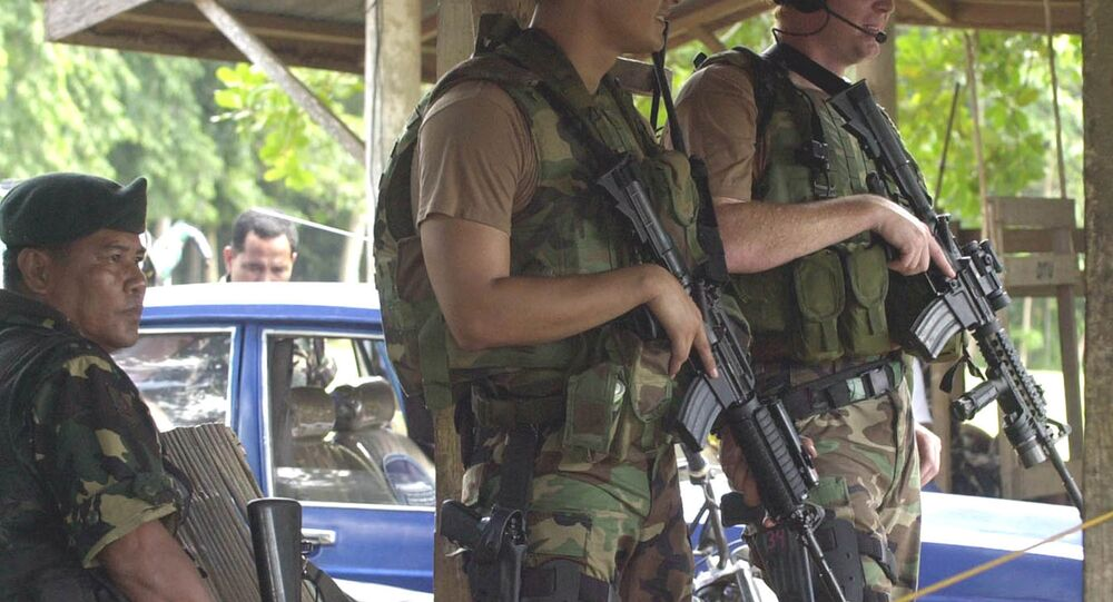 Two U.S. Army Special Forces clutch their M4 carbine beside their Filipino counterpart as they man a checkpoint at the entry of a military base