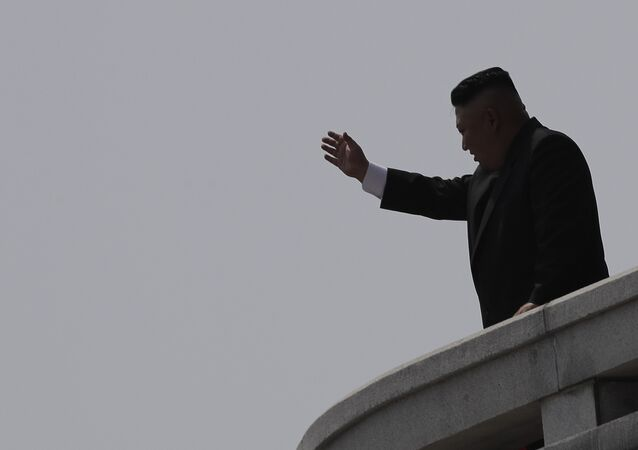 North Korean leader Kim Jong Un is seen in silhouette as he waves during a military parade in Pyongyang, North Korea