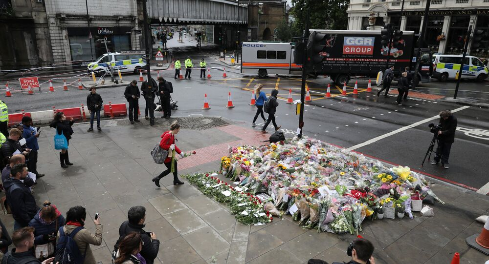 A woman places a rose with other floral tributes for the victims of the attack on London Bridge and Borough Market at London Bridge, London, Britain June 6, 2017