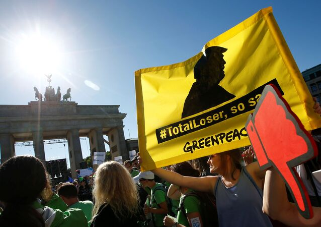 People hold banners as they protest next to the Brandenburg Gate, beside the U.S. embassy, against the U.S. withdrawal from the Paris climate change deal, in Berlin, Germany, June 2, 2017
