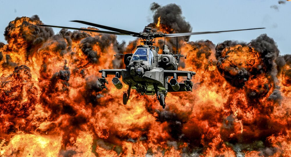 An AH-64D Apache attack helicopter flies in front of a wall of fire during the South Carolina National Guard Air and Ground Expo at McEntire Joint National Guard Base, South Carolina, U.S. on May 6, 2017