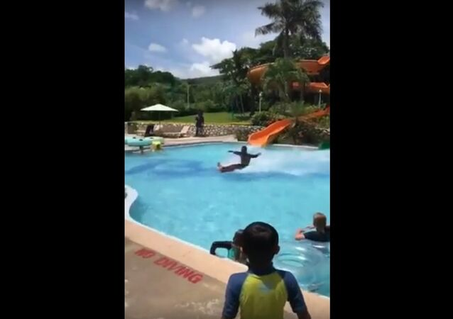 Guy skims across the pool to the end, shoots up, puts on a shirt and walks away