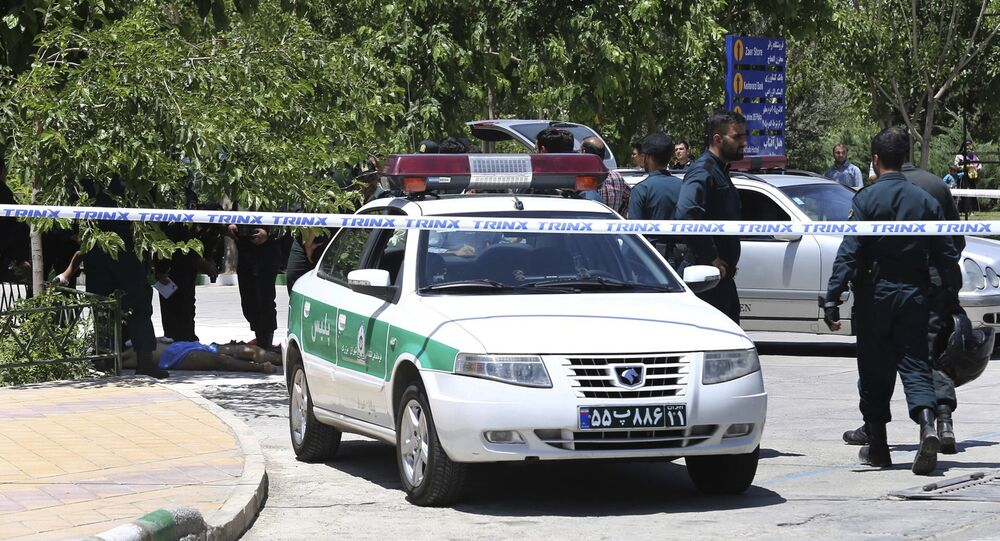 The body of a suspected terrorist, at background left, lies on the ground while police control the scene at the shrine of late Iranian revolutionary founder Ayatollah Khomeini, just outside Tehran, Iran, Wednesday, June 7, 2017