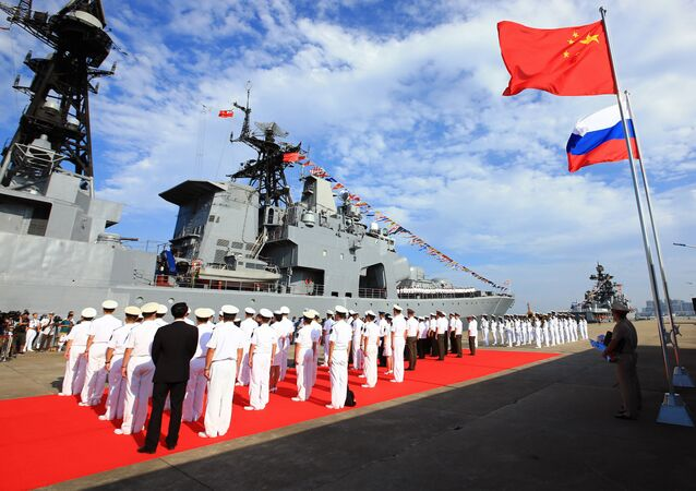 In this photo released by China's Xinhua News Agency, officers and soldiers of China's People's Liberation Army (PLA) Navy hold a welcome ceremony as a Russian naval ship arrives in port in Zhanjiang in southern China's Guangdong Province, Monday, Sept. 12, 2016