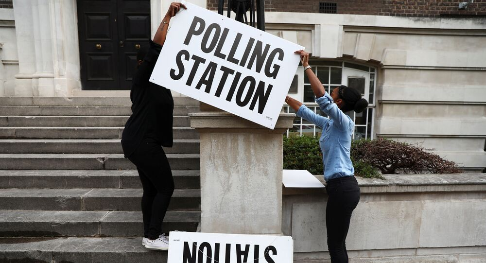 Workers prepare signs outside their polling station on general election day in London, britain, June 8, 2017.