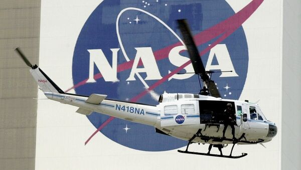 A NASA security helicopter flies by the NASA logo on the Vehicle Assembly Building - Sputnik International