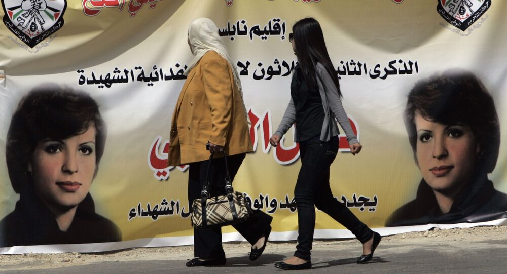 Palestinian women walk past a banner in the West bank town of Bireh, which pictures Fatah member Dalal Mughrabi, who led an attack on an Israeli bus near Tel Aviv, killing 36 people in 1978