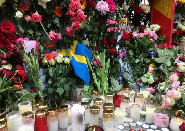 Sweden's flag is seen among flowers near the crime scene in central Stockholm April 8, 2017, the day after a hijacked beer truck plowed into pedestrians on Drottninggatan and crashed into Ahlens department store.