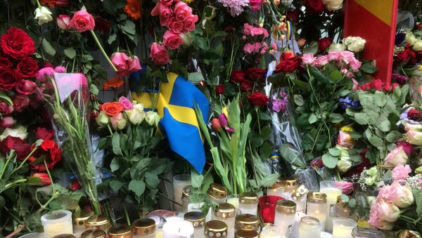 Sweden's flag is seen among flowers near the crime scene in central Stockholm April 8, 2017, the day after a hijacked beer truck plowed into pedestrians on Drottninggatan and crashed into Ahlens department store. - Sputnik International
