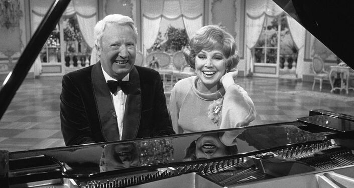 Former British Prime Minister Edward Heath and West German opera singer Anneliese Rothenberger pose sitting at a piano during an interval in shooting for a Television show in Hamburg, West Germany on May 17, 1977.