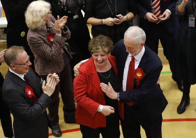 Britain's Labour party leader Jeremy Corbyn, right, tries to high-five with Labour's Emily Thornberry after arriving for the declaration at his constituency in London, Friday, June 9, 2017.