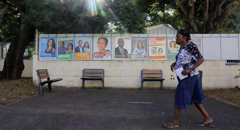 A woman walks past campaign posters as she arrives to a polling station in La Possession on the French Indian Ocean island of La Reunion during the first round of the French legislative elections on June 11, 2017