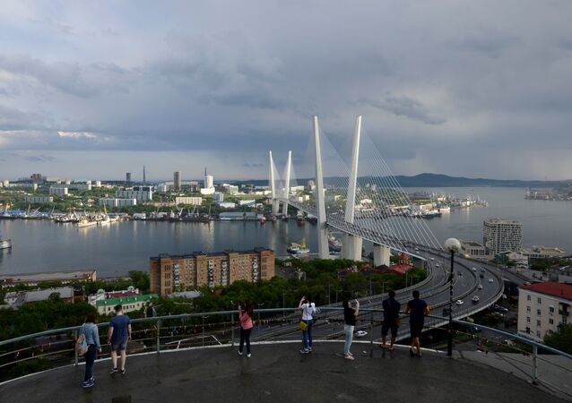 People watch a bridge over the Golden Horn bay from a viewpoint in Vladivostok, Russia, June 8, 2017
