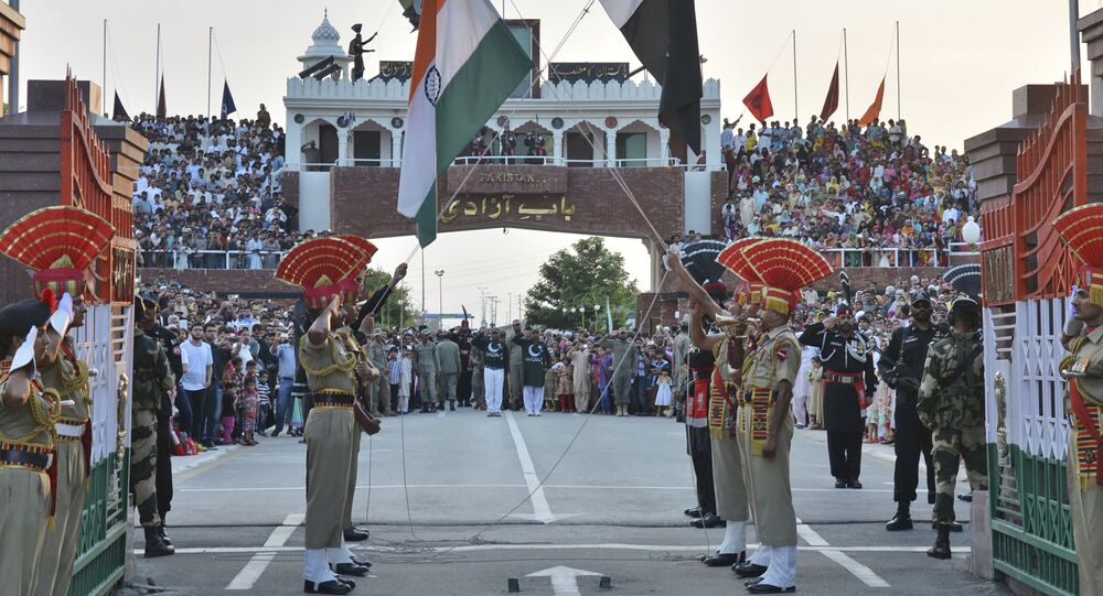 In this July 21, 2015 file photo, Indian and Pakistani flags are lowered during a daily retreat ceremony at the India-Pakistan joint border check post of Attari-Wagah near Amritsar, India