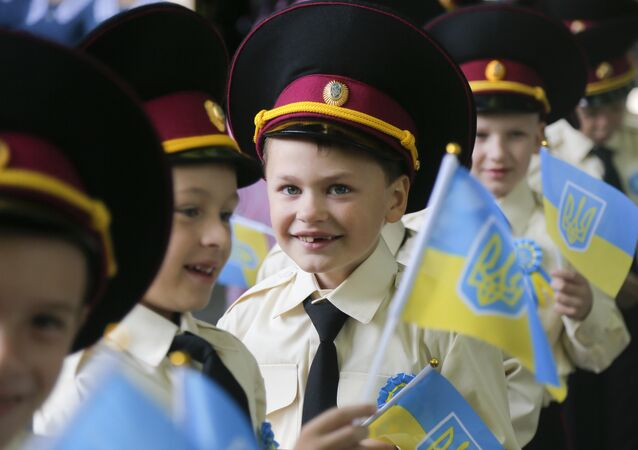 Seven-year old cadets hold Ukrainian flags as they attend a ceremony on the occasion of the first day of school at a cadet lyceum in Kiev, Ukraine, Thursday, Sept. 1, 2016