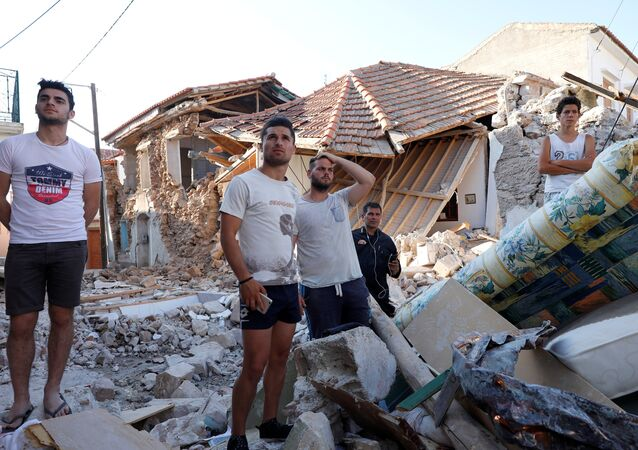 People stand among damaged buildings at the village of Vrissa on the Greek island of Lesbos, Greece, after a strong earthquake shook the eastern Aegean, June 12, 2017.