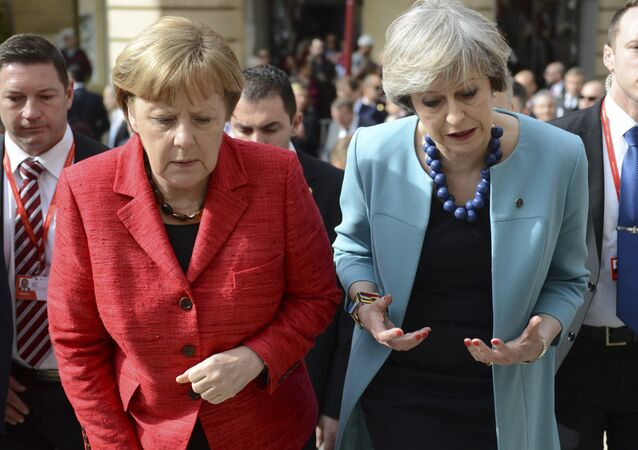 German Chancellor Angela Merkel, left, speaks with British Prime Minister Theresa May as they walk with other EU leaders during an event at an EU summit in Valletta, Malta, on Friday, Feb. 3, 2017.