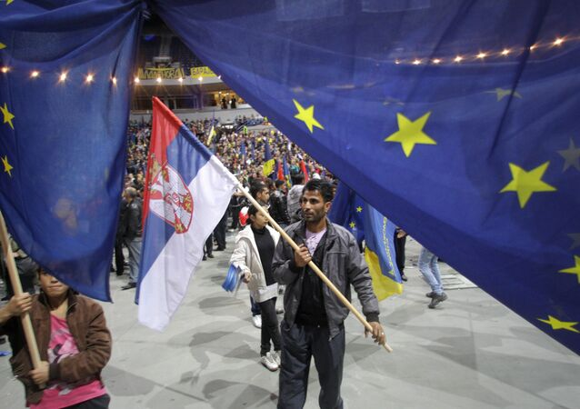 Supporter of Pro-Western former Serbian President and presidential candidate Boris Tadic waves with Serbian , center, and EU flags during a final pre-election rally in Belgrade, Serbia, Thursday, May 17, 2012.