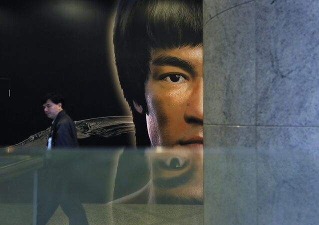 A man walks past a promotional poster of Bruce Lee's memorial exhibition at the Hong Kong Heritage Museum in Hong Kong, Monday, March 31, 2014, to mark the 40th anniversary of the death of Lee