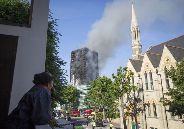 Smoke billows from a high-rise apartment building on fire in London, Wednesday, June 14, 2017