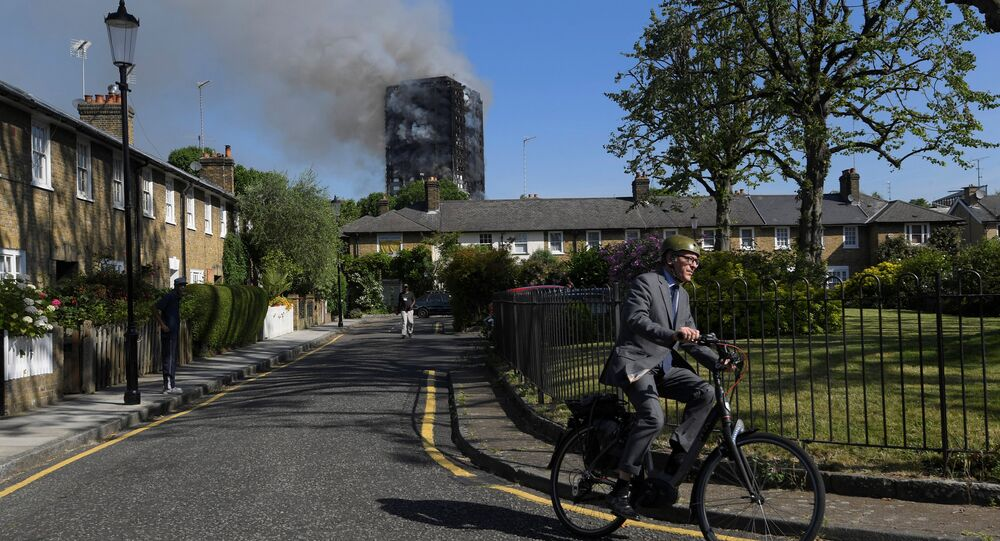 A cyclist rides near a tower block severly damaged by a serious fire, in north Kensington, West London, Britain June 14, 2017