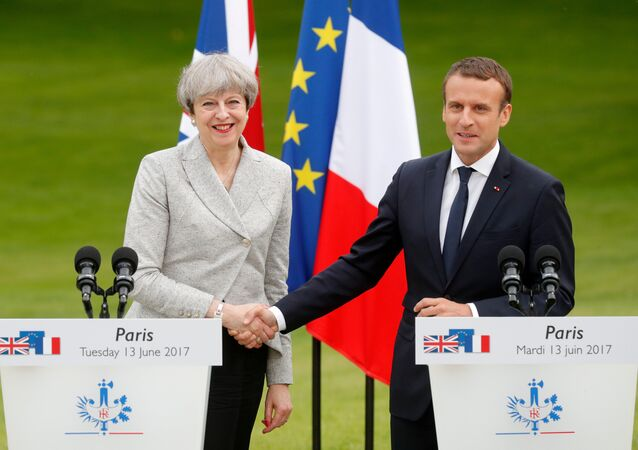 French President Emmanuel Macron (R) and Britain's Prime Minister Theresa May shake hands after they spoke to the press at the Elysee Palace in Paris, France, June 13, 2017.