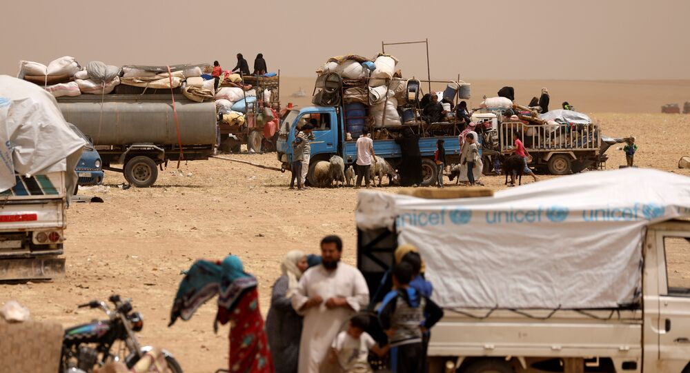 Internally displaced people who fled Raqqa city gather near vehicles carrying their belongings in a camp near Ain Issa, Raqqa Governorate, Syria May 19, 2017