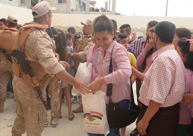 Officers distribute humanitarian aid in Latakia Governorate, Syria