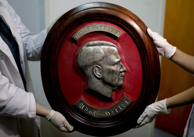 Members of the federal police show a bust relief portrait of Nazi leader Adolf Hitler at the Interpol headquarters in Buenos Aires, Argentina, Friday, June 16, 2017.