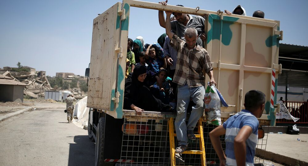 Civilians fleeing the fighting between the Iraqi forces and Islamic State militants arrive at a processing centre before being transferred to refugee camps, in western Mosul, Iraq June 19, 2017
