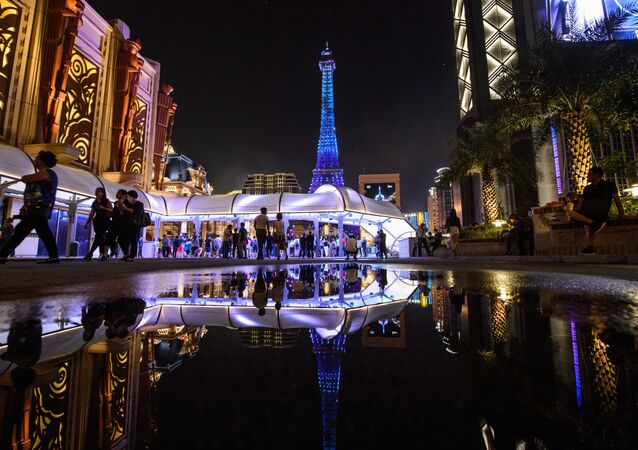 Tourists look at a replica of the Eiffel Tower after the opening of the Sands new mega resort The Parisian in Macau, on September 13, 2016. Billionaire casino tycoon Sheldon Adelson predicted a revival for beleaguered Macau as he launched his new Paris-themed mega resort, with the gambling enclave betting its fortunes on mass market tourists.