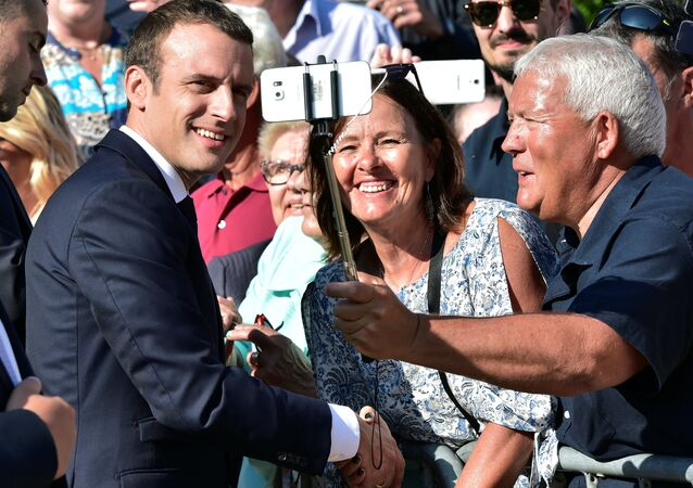 French President Emmanuel Macron (L) poses for a selfie after he voted in the second round parliamentary elections in Le Touquet, France, June 18, 2017