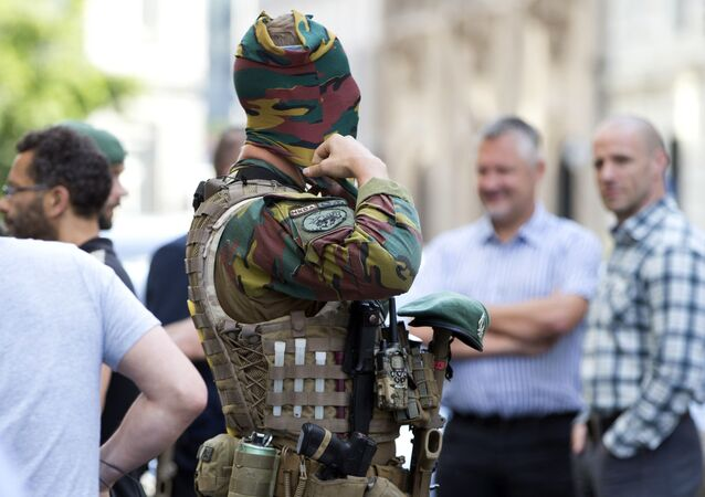 A Belgian Army soldier adjusts his face mask as he patrols outside the prime ministers office in Brussels on Wednesday, June 21, 2017.