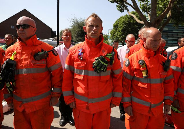 Members of the emergency services attend a minute's silence for the victims of the Grenfell Tower fire near the site of the blaze in North Kensington, London, Britain, June 19, 2017.