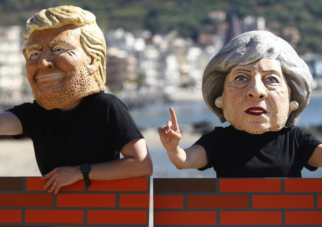 Protesters wear masks depicting U.S. President Donald Trump and Britain's Prime Minister Theresa May during a demonstration against a G7 summit organised by Oxfam in Giardini Naxos near Taormina, Sicily, Italy, May 27, 2017.