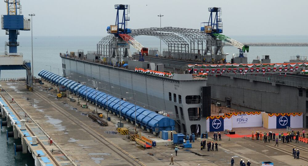 Indian workers stand alongside the FDN-2 Indian Navy floating dock as it is launched at a shipyard in Chennai on June 20, 201