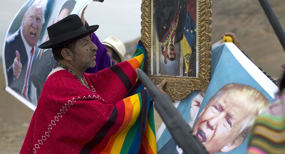 A shaman performs a ceremony holding a portrait of Venezuela's President Nicolas Maduro upside down, as another holds a poster of U.S. President Donald Trump, on Morro Solar in Lima, Peru, Monday, June 12, 2017