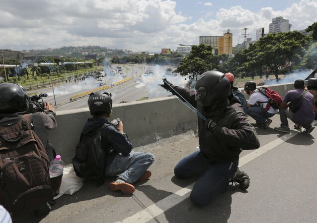 An anti-government demonstrator aims a slingshot during clashes with security forces along a highway in Caracas, Venezuela, Monday, June 19, 2017