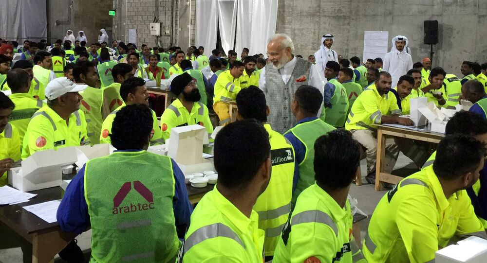 In this Saturday June 4, 2016 photo released by the Indian Prime Minister's Tweeter, Indian Prime Minister Narendra Modi, center, meets with hundreds of Indian laborers at a workers' camp in the capital Doha, Qatar