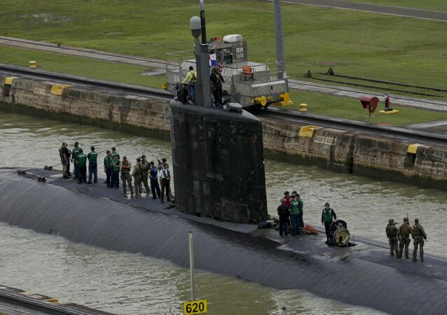 Crew members stand on top of USS Columbus (SSN-762) submarine as they sail through the Panama Canal's Miraflores Locks en route to the Pacific Ocean in Panama City, Friday, July 10, 2015