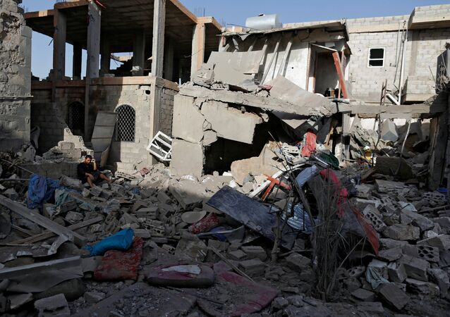 A man sits on the rubble of a house of his relatives, destroyed by a Saudi-led air strike in Sanaa, Yemen June 9, 2017