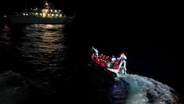Fiorillo Italian Coast Guard vessel officers transfer migrants being rescued by Save the Children NGO crew from the ship Vos Hestia, in the Mediterranean sea off the Libyan coast, June 16, 2017 - Sputnik International