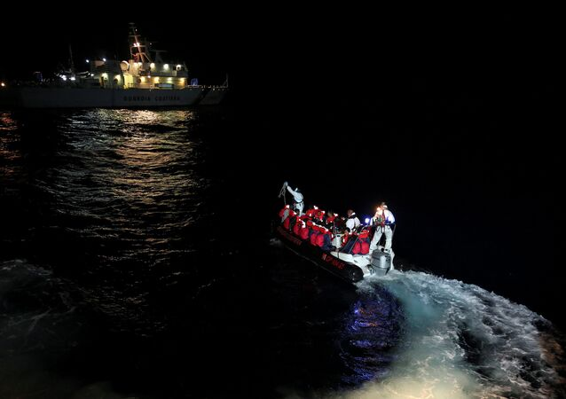 Fiorillo Italian Coast Guard vessel officers transfer migrants being rescued by Save the Children NGO crew from the ship Vos Hestia, in the Mediterranean sea off the Libyan coast, June 16, 2017