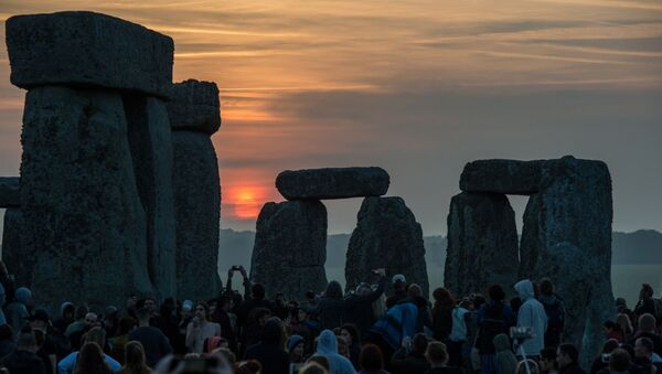 Revellers watch the sunrise as they celebrate the pagan festival of Summer Solstice at Stonehenge in Wiltshire, southern England on June 21, 2017 - Sputnik International
