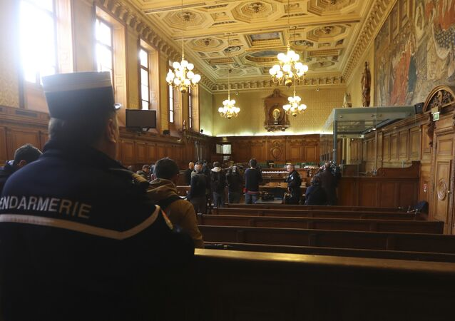 A gendarme looks on (L) as reporters work next to a bulletproof dock in the courtroom of a Special Court of Assizes at the Paris courthouse, prior to the start of the trial of a jihadist cell known as the Cannes-Torcy cell, long considered one of the most dangerous in France, on April 20, 2017