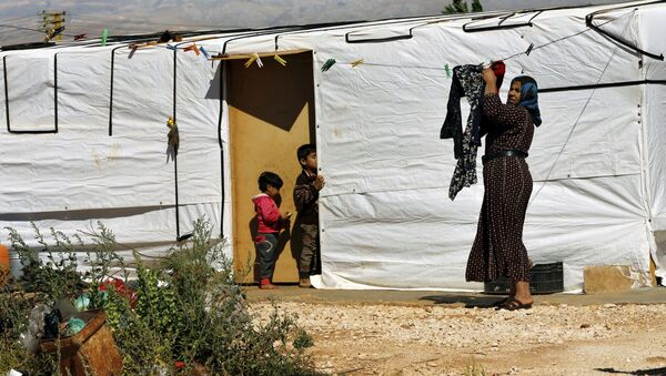 A Syrian refugee woman hangs laundry outside her tent at a Syrian refugee camp in the eastern city of Baalbek, Lebanon, Tuesday, June 20, 2017 - Sputnik International